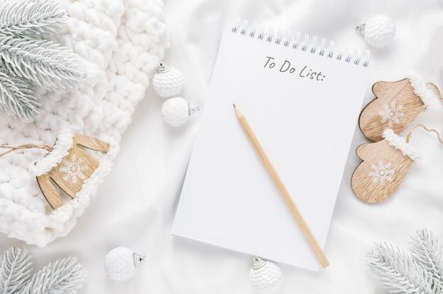 Décorations de noël et bloc-notes avec liste de tâches sur blanc