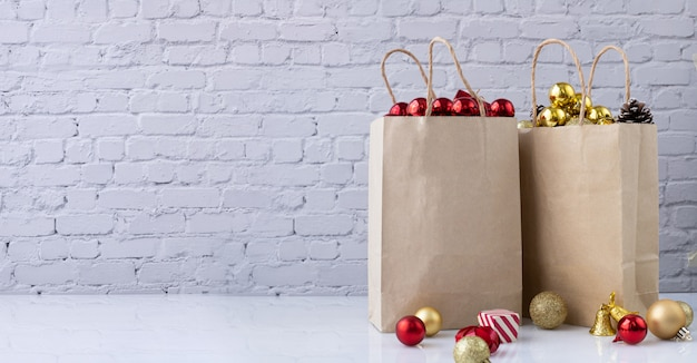 Décorations de noël avec une boule rouge et or dans des sacs à provisions en papier kraft.