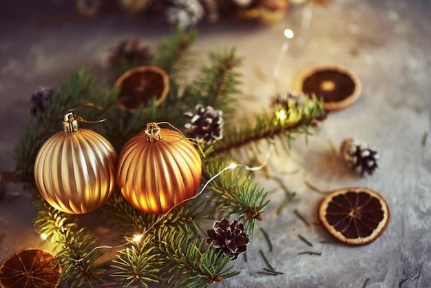 Décorations de noël avec des boules d'or, une branche de sapin et des guirlandes lumineuses sur fond sombre
