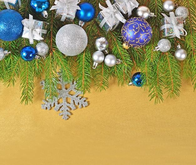 Décorations de noël sur une branche d'épinette sur fond doré