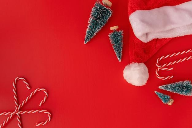 Décorations de noël cannes de bonbon, sapins et chapeau de sants vue de dessus sur rouge