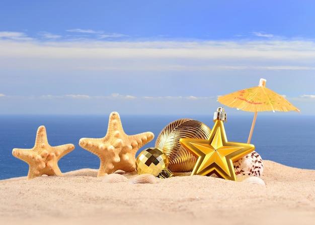 Décorations de noël, coquillages et étoiles de mer sur le sable d'une plage sur fond de mer