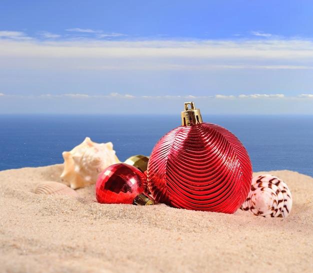 Décorations de noël et coquillages sur le sable d'une plage sur fond de mer