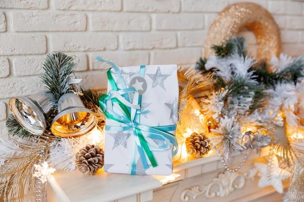 Décorations de noël et du nouvel an sur la cheminée. fond d'hiver de vacances avec cadeau emballé. cadeau avec un arc en papier.