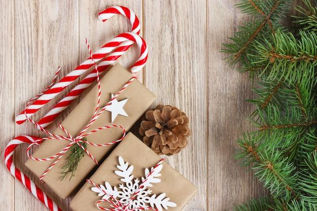 Décorations de noël ou du nouvel an avec des pommes de pin, des branches de sapin, des coffrets cadeaux et des bonbons sur blanc