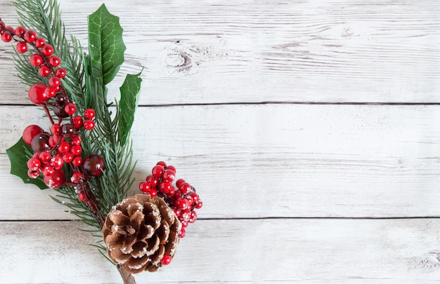 Décorations de noël faites de branches d'épinette aux fruits rouges et pommes de pin naturelles brunes sur un fond en bois clair.