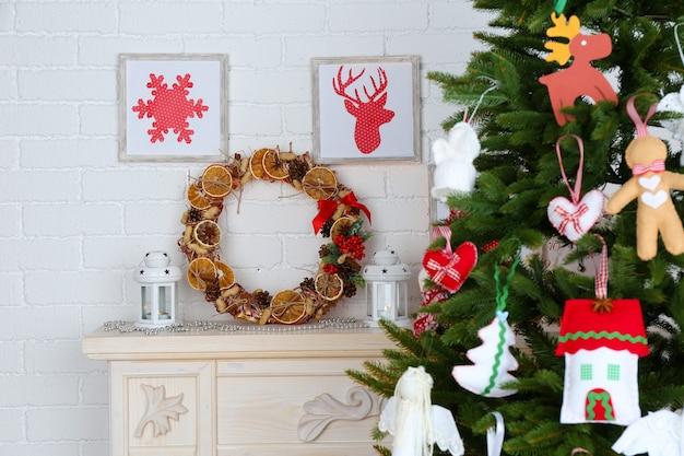 Décorations de noël faites à la main sur l'arbre de noël sur l'intérieur de la maison lumineuse