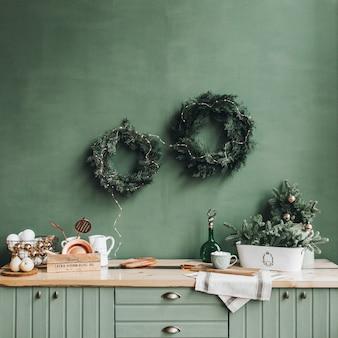 Décorations de noël festives dans la cuisine avec une couronne faite à la main de branches de sapin, de jouets dorés et blancs