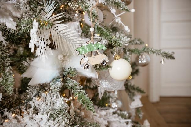 Décorations de noël, flocon de neige argenté, boules blanches, jouets en bois sur un arbre de noël gros plan.