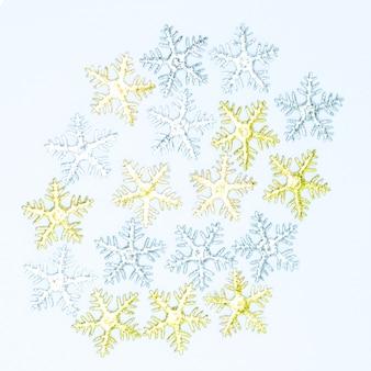 Décorations de noël, flocons de neige argentés et flocons de neige dorés sur fond blanc.