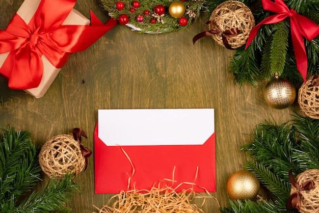 Décorations de noël sur fond texturé en bois vert, vue de dessus, espace libre pour la conception, lettre dans une enveloppe rouge