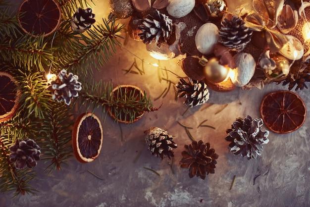 Décorations de noël avec guirlandes lumineuses, pommes de pin et branche de sapin