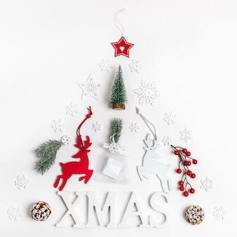 Décorations de noël lettres xmas, cerf, brindilles de sapin, baies rouges, flocons de neige et cadeau de bricolage disposé comme arbre de noël sur blanc