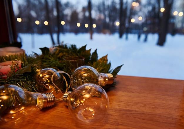 Décorations de noël. ornement sur une branche de pin avec des bougies et des lampes avec des lumières sur un fond couvert de neige. vue depuis la fenêtre.
