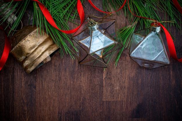 Décorations de noël en verre délicates, ruban rouge et branches naturelles de pin (épicéa) sur fond en bois.