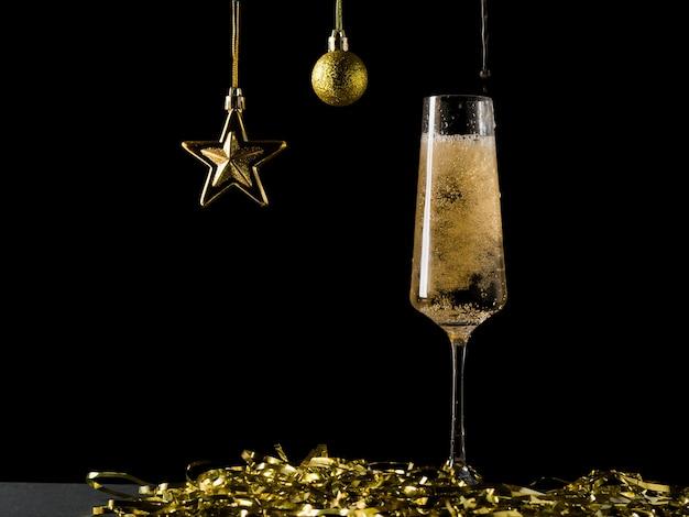 Décorations de noël et vin mousseux bouillonnant dans un verre. une boisson alcoolisée populaire.