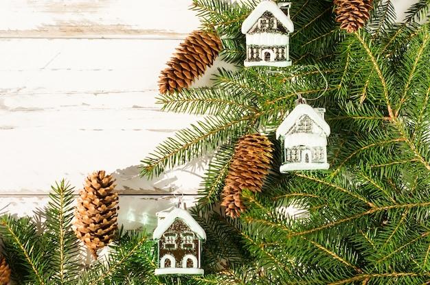 Décorations de nouvel an et de noël sur des branches d'épinette. cônes et jouets forestiers naturels - maisons enneigées. fond en bois blanc. vue de dessus.