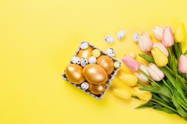 Décorations de pâques. oeufs d'or décoratifs, brindilles de saule et tulipes sur fond jaune