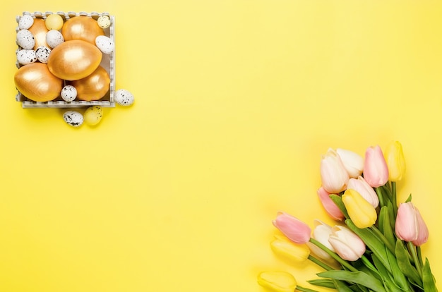 Décorations de pâques. oeufs de pâques décoratifs, brindilles de saule et tulipes sur fond jaune