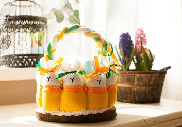 Décorations de pâques - panier textile avec lapins et œufs, lumière du matin par la fenêtre