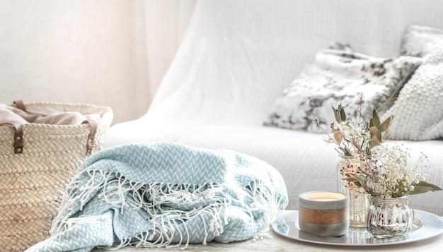 Décorations pour la maison à l'intérieur. une couverture turquoise et un panier en osier avec un vase de fleurs et de bougies