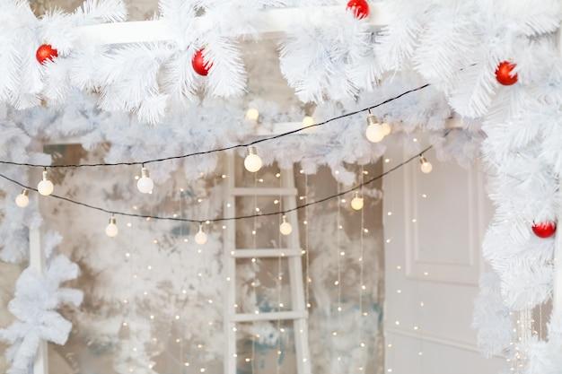 Décorations pour la nouvelle année en blanc et une guirlande scintillante. décorations dans la maison pour noël.