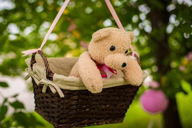 Décorations de rue pour une fête d'enfants. un panier avec un ours en peluche dans un ballon à air dans un parc verdoyant.