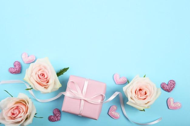 Décorations de la saint-valentin, bouquet et cadeau sur fond bleu