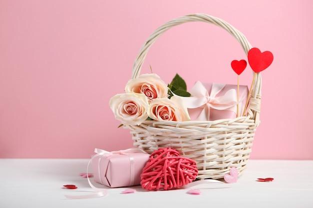 Décorations de la saint-valentin et panier-cadeau sur fond rose