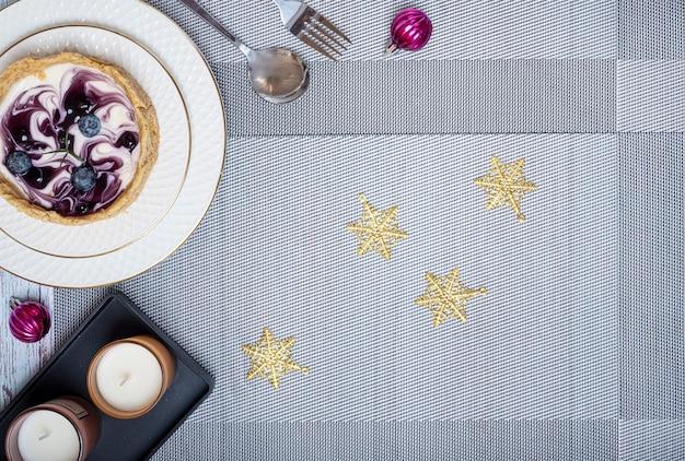 Décorations de table de dîner de noël avec un morceau de gâteau au fromage aux bleuets