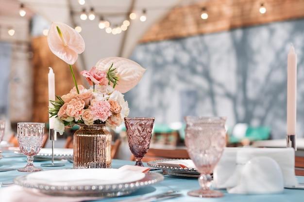 Décorations de table de fleurs pour les vacances et le dîner de mariage. set de table pour la réception de mariage de vacances dans un restaurant en plein air.