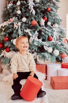 Décorations de vacances d'hiver. couleurs chaudes. belle petite fille joue avec des boîtes à cadeaux
