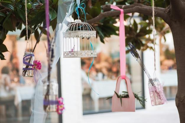 Décorations vintage de mariage avec des cages blanches décoratives et des fleurs sur un arbre.