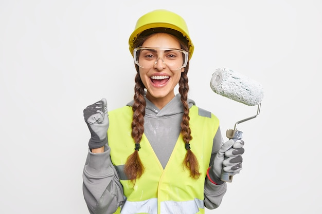 Une décoratrice positive serre le poing de joie tient un rouleau de peinture prêt pour la rénovation de la chambre