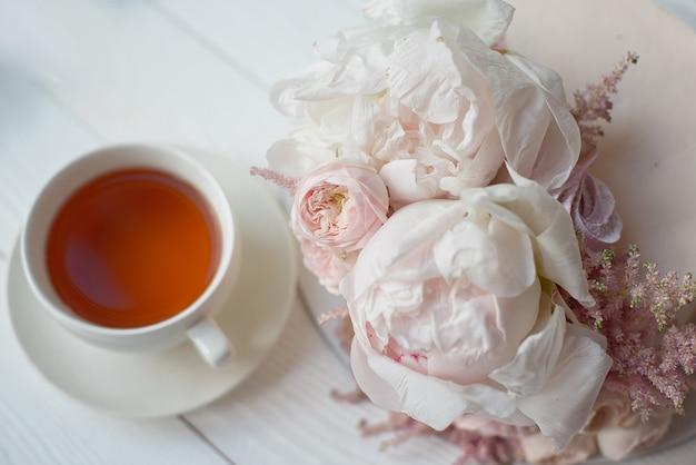 Décoré avec des fleurs fraîches, un gâteau nude blanc, un gâteau élégant pour les mariages et les événements une tasse blanche avec une boisson chaude