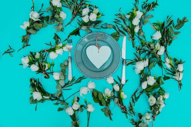 Décorées de roses blanches et ustensiles en forme de coeur c avec sur fond vert. décoré. vue ci-dessus