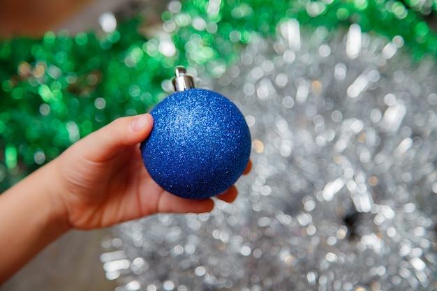 Décorer un arbre de noël à la maison. main tenant ornement boule bleue bouchent sur fond brillant avec des lumières colorées. espace pour le texte.