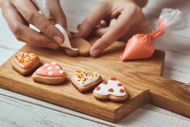 Décorer les biscuits de pain d'épice avec du glaçage. mains de femme décorer des cookies en forme de coeur, gros plan