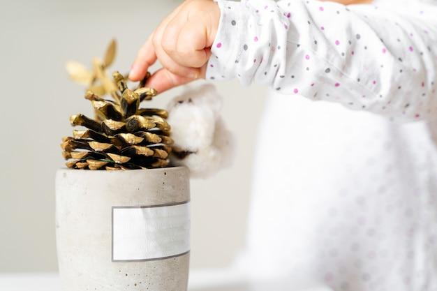 Décorer à la main bébé bambin avec pomme de pin dorée. noël. jouets naturels waldorf