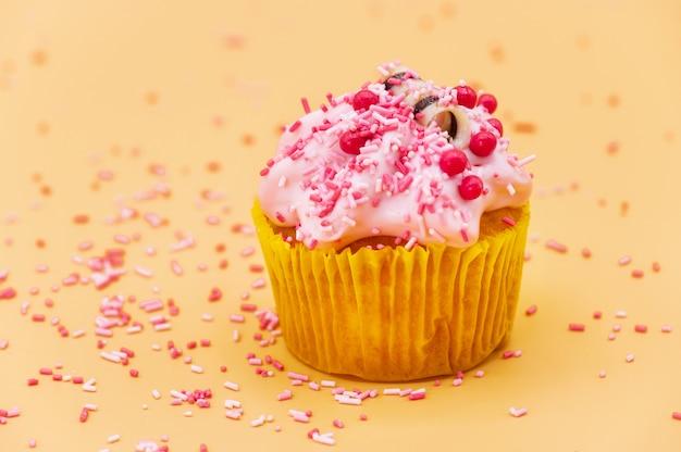Décorer un petit gâteau avec des paillettes sur fond pastel orange.