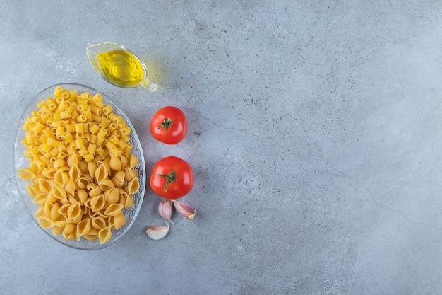 Décortiquer les pâtes crues avec du ditali rigati sec cru dans un bol en verre avec des tomates rouges fraîches et de l'ail.