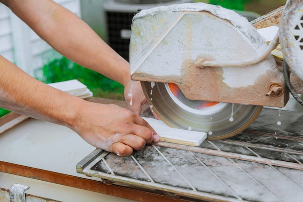 Découpe manuelle de carreaux de céramique sur une machine spéciale pour la découpe de carreaux.