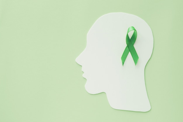 Découpe de papier cerveau avec ruban vert sur fond vert, concept de santé mentale, journée mondiale de la santé mentale
