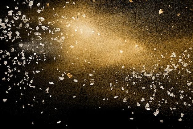Découper des débris de pierre explosant avec du sable doré de rivière sec sur un fond noir.