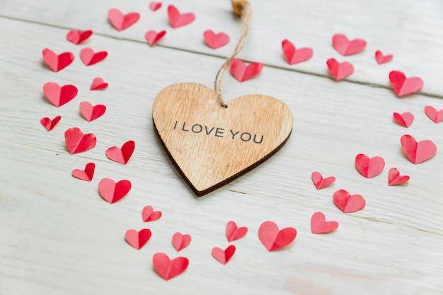 Découper du papier petits coeurs et coeur en bois avec l'inscription je t'aime
