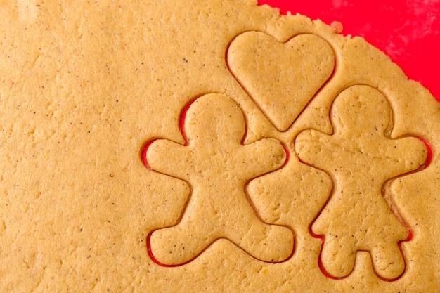 Découper des formes de pain d'épice. concept de couple familial ou amoureux de la pâte pour la saint-valentin.