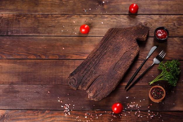 Découper une planche de bois ainsi que des légumes et une table sombre spéciale. préparation pour la production alimentaire