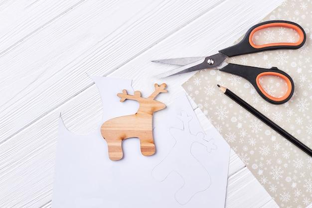 Découpez un cerf en bois, des ciseaux, un crayon.