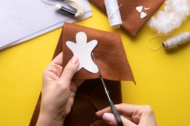 Découpez les détails du bonhomme en pain d'épice de noël du feutre au motif. instructions de fabrication étape par étape. étape 2.
