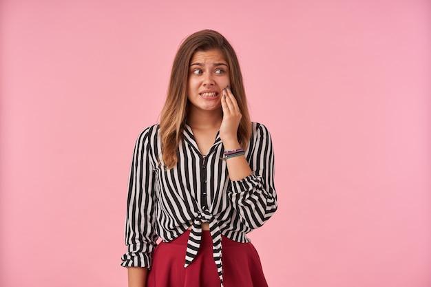 Découragé jeune femme aux cheveux bruns tenant la main levée sur sa joue et fronçant les sourcils tout en regardant perplexe de côté, portant des vêtements de fête tout en posant sur rose